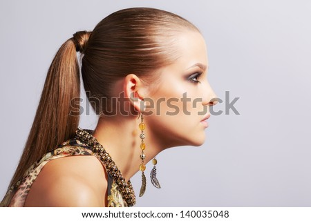 sideview portrait of beautiful young long-haired brunette woman in ear-rings on gray - stock photo