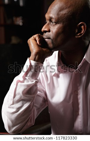 Sideview portrait of pensive african man in pink shirt - stock photo
