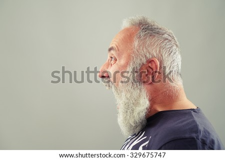 sideview portrait of screaming senior man with grey-haired beard