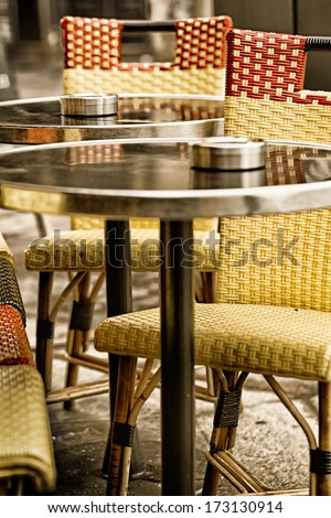 Sidewalk cafe chairs and tables toned in vintage colors. Location: Paris, France
