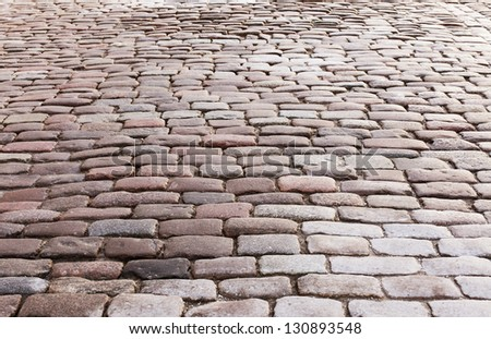 Sidewalk covered with old paving stones - stock photo