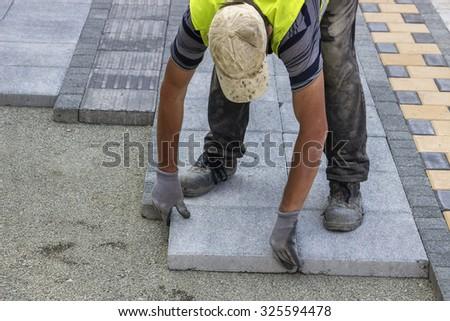 Sidewalk paver installation in progress. Sidewalk revitalization. Focus on worker. - stock photo