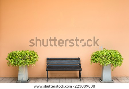 sidewalk scene with wooden bench and orange wall with tree - stock photo