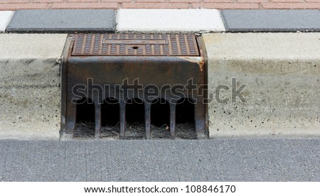 Sidewalk with a street drainage and road - stock photo