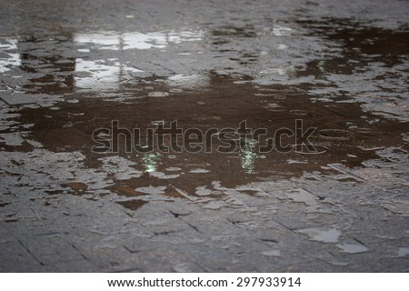 Sidewalk with puddles of water and raindrops - stock photo