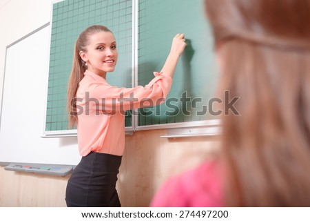 Sideward glance. Young female teacher is going to write on green blackboard and looking at pupil - stock photo