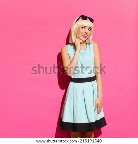 Sideways glance. Smiling young woman standing in a sunlight against pink wall, holding hand on chin and looking away. Three quarter length studio shot on pink background. - stock photo