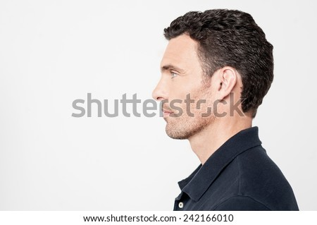 Sideways of a young man looking at copy space - stock photo