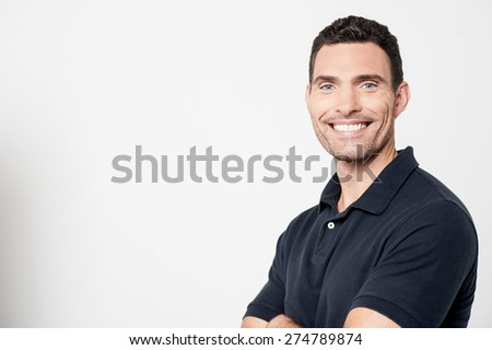Sideways of smiling man with arms crossed - stock photo