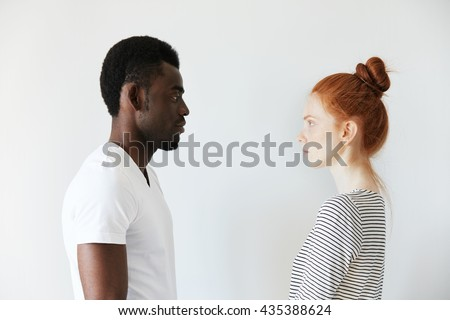 Sideways portrait of a couple looking each other in the eyes on white background. Afro man standing still and Caucasian redhead girl as well watching him with serious look like wife on husband. - stock photo