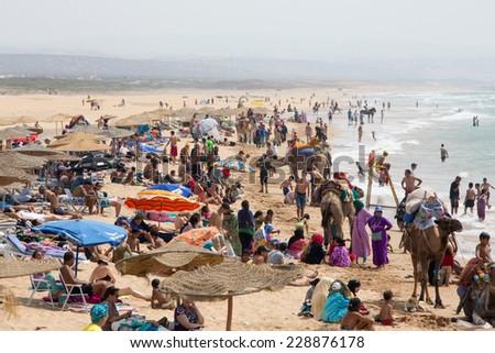 SIDI KAOUKI, MOROCCO - AUGUST 25: Beautiful beach full of vacationing people on 25 August 2014 in Sidi Kaouki near Essaouira, Morocco. Sidi Kaouki is a small town and rural commune in Essaouira. - stock photo