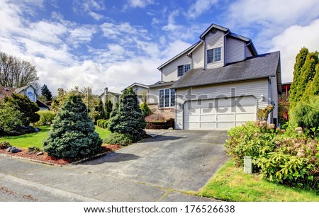 Siding house with garage. Green lawn with trimmed hedges, flourishing bushes and fir trees. - stock photo