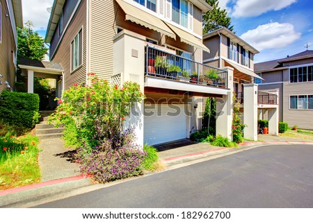 Siding residential building with balcony and garage. View of walkway and entrance porch