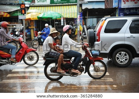 SIEM REAP, CAMBDODIA - AUG 12, 2013: Traffic moves along a busy city centre road. In poverty stricken Cambodia only about 50 percent of the roads and highways are covered with asphalt - stock photo