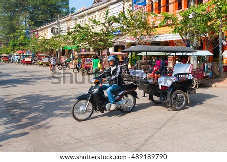 SIEM REAP, CAMBODIA - 23 DEC 2013: Empty tuk tuk taxi towing a trailer with no people in passes a street