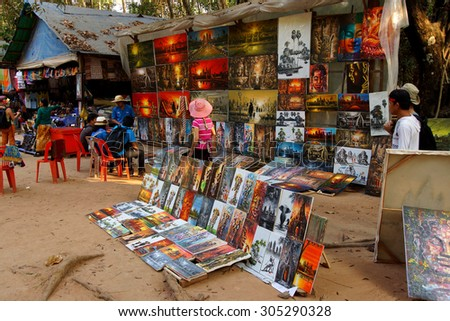 SIEM REAP, CAMBODIA - FEB 14, 2015 - Tourists shop for paintings of Angkor Wat,   Cambodia - stock photo
