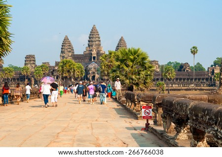 SIEM REAP, CAMBODIA - FEBRUARY 18, 2014: The main temple of Angkor Wat, seen from the causeway on the western approach, draws thousands of visitors worldwide to this monument of the Khmer empire. - stock photo