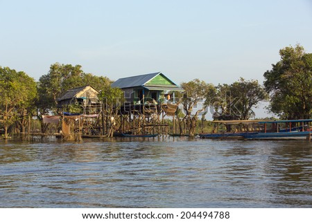 SIEM REAP, CAMBODIA - JAN 2: Floating village on the bank of Tonle Sap Lake in Siem Reap, Cambodia on January 2, 2014. Tonle Sap is the largest freshwater lake in SE Asia peaking at 16k km2.