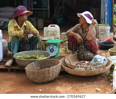 SIEM REAP, CAMBODIA - NOVEMBER 23: Two Cambodian women sitting with their goods for sale at a local market near Siem Reap, Cambodia on the 23rd November, 2013.