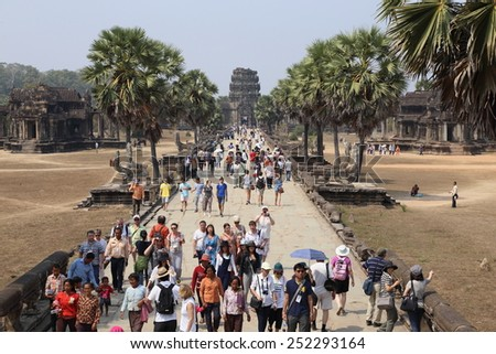 SIEM REAP - February 13: Large crowds of tourists gather to visit the ruins of Angkor Wat, one of the most popular tourist destinations in Asia February 13, 2015 Siem Reap Cambodia. - stock photo