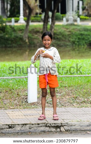 SIEM RIEP, CAMBODIA - SEP 28, 2014: Unidentified Khmer girl smiles and eats candy in Siem Reap. 90% of Cambodian people belong to Khmer etnic group