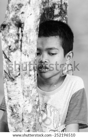 SIEM RIEP, CAMBODIA - SEP 28, 2014: Unidentified Khmer little boy stays near a tree in Siem Reap. 90% of Cambodian people belong to Khmer etnic group