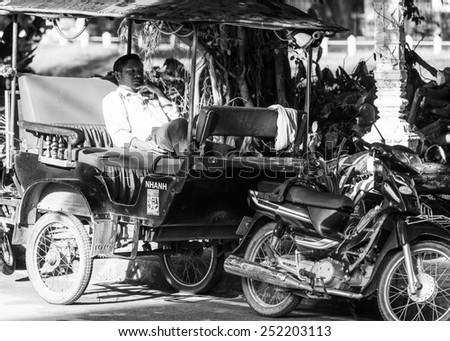 SIEMREAP, CAMBODIA - SEP 26, 2014: Unidentified Khmer man in a local taxi called taktak in the street. 90% of Cambodian people belong to Khmer etnic group