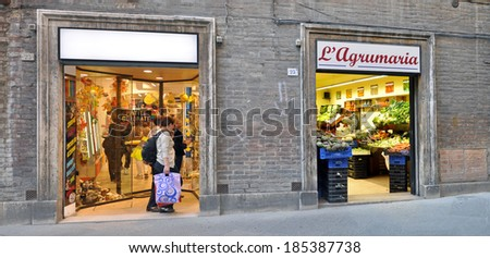 SIENA, ITALY - APRIL 18: Tourists at a shop window in Siena, Italy on April 18, 2011. Historic center of Siena was declared by UNESCO a World Heritage Site.