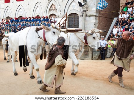 "SIENA, ITALY - AUGUST 16: Parade before start of annual traditional Palio di Siena horse race in medieval square ""Piazza del Campo"" August 16, 2014 in Siena, Italy. - stock photo"