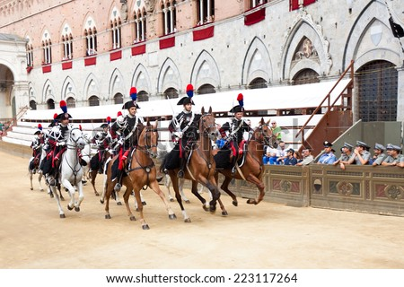 "SIENA, ITALY - AUGUST 16: Performance of cavalry on parade before start of annual traditional Palio di Siena horse race in medieval square ""Piazza del Campo"" August 16, 2014 in Siena, Italy - stock photo"