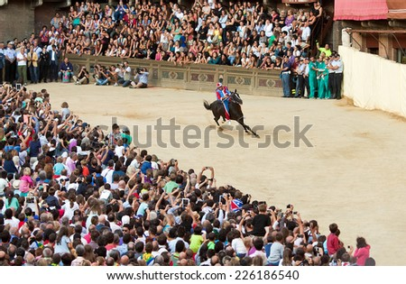 "SIENA, ITALY - AUGUST 15: Preliminary races ""Palio di Siena"" in medieval square ""Piazza del Campo"" on August 15, 2014 in Siena, Italy. Race is held twice every year - stock photo"