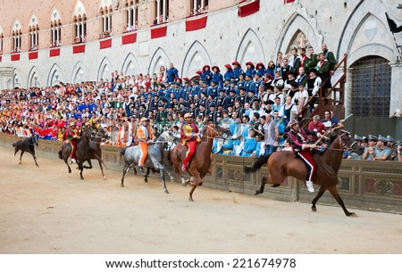 "SIENA, ITALY - AUGUST 16: Riders compete in horse race ""Palio di Siena"" in  medieval square ""Piazza del Campo"" on August 16, 20014 in Siena, Italy. The race is held twice every year - stock photo"