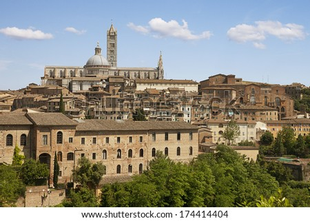 Siena's Duomo, one of Italy's most beautiful cathedrals, and it's marble-striped bell tower, with residential buildings below.  - stock photo