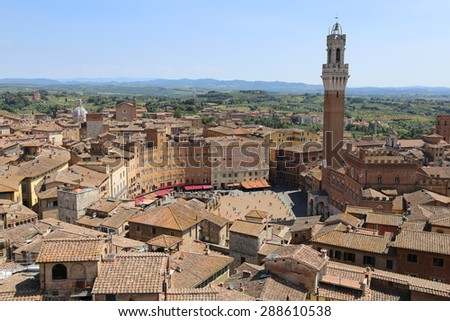 Siena, Tuscany. Aerial view from above the ancient rooftops of the beautiful medieval city to piazza di campo, the heart of the city and the main focus of the picture. - stock photo