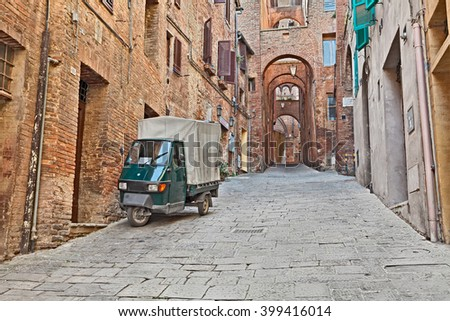 SIENA, TUSCANY, ITALY - MARCH 22: picturesque Italian alley in the old town with ancient dwellings, archs and three-wheeled vehicle Ape Piaggio, on March 22, 2016 in Siena, Tuscany, Italy