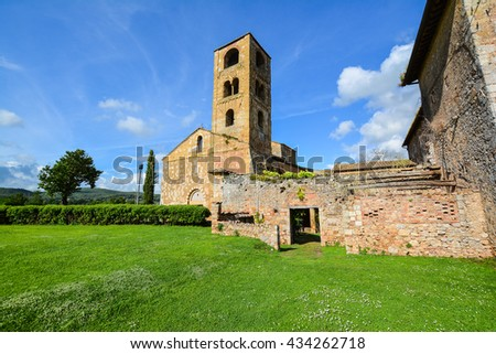 SIENNA, ITALY - MAY 31, 2016 - Romanesque bell tower of the church in brown stone in the province of Siena in Tuscany