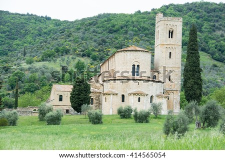 SIENNA, ITALY - MAY 01, 2016 - sant'antimo the church in the hills of green wheat with a gray sky in the Val d' Orcia in Tuscany sienna