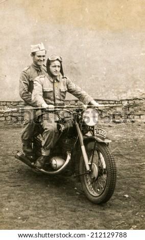 SIERADZ, POLAND, CIRCA SIXTIES - Vintage photo of two men on motorbike - stock photo