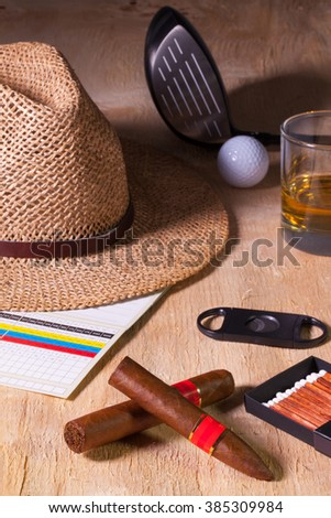 Siesta - cigar, straw hat,Scotch whiskey and golf driver on a wooden table - stock photo
