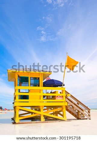 Siesta Key Beach on the west coast of Florida is famous for the fine white sand. Typical lifeguard house in bright color with a flag. - stock photo
