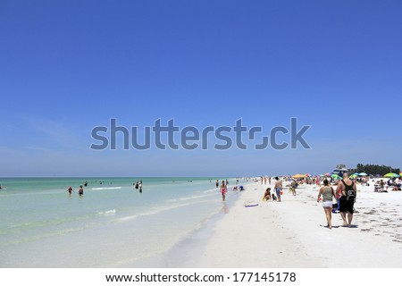 SIESTA KEY, FLORIDA - MAY 9, 2013: Many people relaxing at the sunny and beautiful white quartz sand Siesta Beach located in the Gulf of Mexico. - stock photo