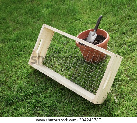 Sieve with a wooden frame for garden works and scoop