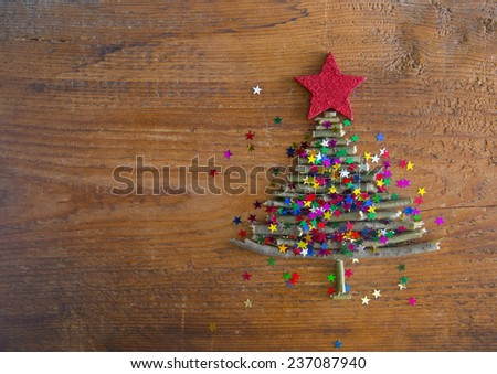 Sigh symbol from many dry Stick Christmas green Tree and a lot colorful star toys on old retro vintage style wooden texture background Empty copy space for inscription Idea of merry new year holiday - stock photo
