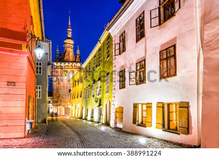 Sighisoara in Romania. Night view of clock tower in historic medieval city. Vlad Tepes, Dracula, was born here. - stock photo