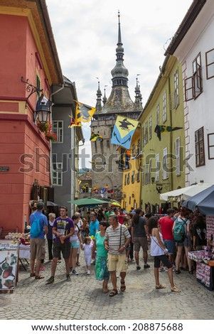 SIGHISOARA, ROMANIA - JULY 26, 2014: Crowd of tourists visit the famous medieval citadel of Sighisoara, listed by UNESCO as World Heritage Site. Vlad Tepes (Dracula) was born here in 1431. - stock photo
