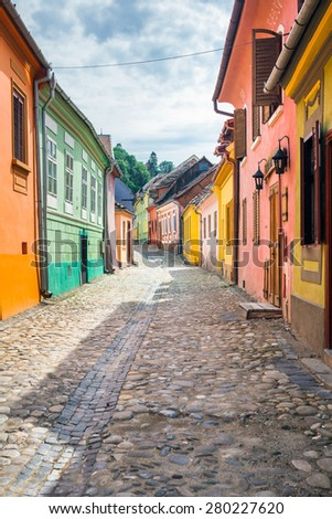 Sighisoara, Romania - June 23, 2013: Stone paved old streets with colored houses from Sighisoara fortresss, Transylvania, Romania - stock photo