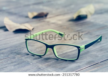 Sight glasses and dried leafs on bamboo floor in vintage - stock photo