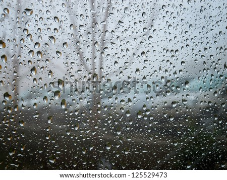 Sight to the moody and  rainy day through raindrops on a window