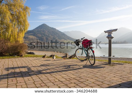 sightseeing at promenade lake schliersee in autumn, trekking bike and spyglass - stock photo