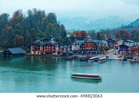 Sightseeing boats cruising on Konigssee ( King's Lake ) with autumn trees & boathouses by lakeside at foggy misty blue dusk ~ Beautiful fall scenery of Bavarian countryside in Berchtesgaden Germany